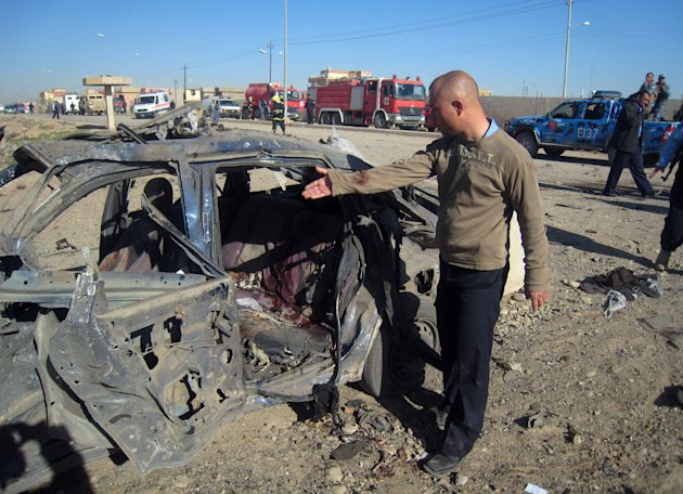 A man gestures at a destroyed vehicle at the scene of a car bomb attack in Kirkuk, 290 kilometers (180 miles) north of Baghdad, Iraq, Tuesday, March 20, 2012. Officials say attacks across Iraq have killed and wounded scores of people, police said, in a spate of violence that was dreaded in the days before Baghdad hosts the Arab world's top leaders. (AP Photo/Emad Matti)