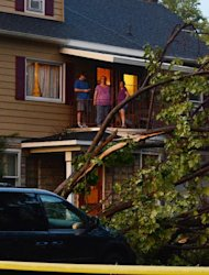A family surveys the damage surrounding their property in Elmira N.Y., after a possible tornado struck the area, Thursday, July 26, 2012. The storm brought down trees and power lines, tore roofs off some buildings and caused motor vehicle accidents. Utilities report more than 20,000 customers without power in the area. (AP photos/Heather Ainsworth)