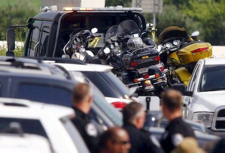 Police officers look at several motorcycles at the Twin Peaks restaurant, where nine members of a motorcycle gang were shot and killed, in Waco