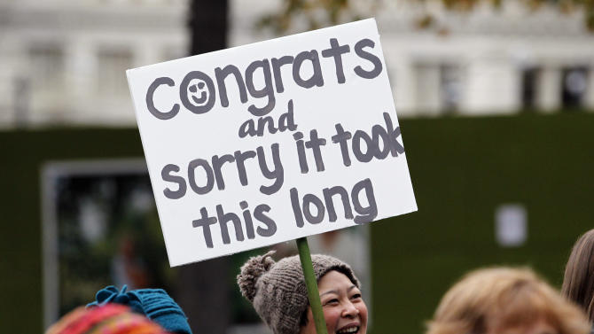 Cindy Ogasawara stands with other well-wishers greeting newly married couples as they depart Seattle City Hall, Sunday, Dec. 9, 2012, in Seattle. Gov. Chris Gregoire signed a voter-approved law legalizing gay marriage Wednesday, Dec. 5 and weddings for gay and lesbian couples began in Washington on Sunday, following the three-day waiting period after marriage licenses were issued earlier in the week. (AP Photo/Elaine Thompson)