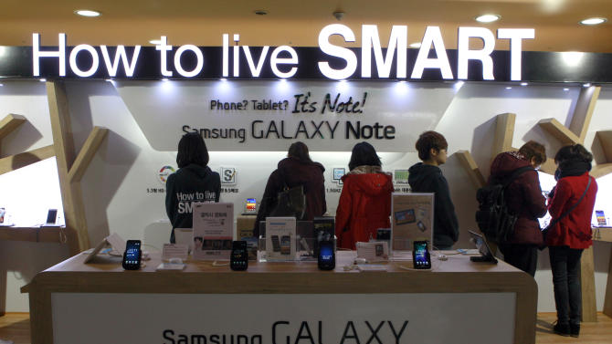 Shoppers look at Samsung Electronics devices at the company's showroom in Seoul, South Korea, Friday, Jan. 27, 2012. Samsung Electronics Co. reported a 17 percent jump in fourth quarter profit on the strength of sales in flat panels and smartphones even as the company battled claims it had copied Apple's iPhone. (AP Photo/ Lee Jin-man)