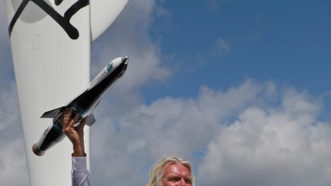 "British billionaire Richard Branson poses for the photographers in the window of a replica of the Virgin Galactic, which according to the company will be the world's first commercial spaceline, at the Farnborough International Airshow in  Farnborough, England, Wednesday,  July 11, 2012. Virgin Galactic announced ""LauncherOne,"" a new air-launched rocket specifically designed to deliver small satellites into orbit. Commercial flights of the new orbital launch vehicle are expected to begin by 2016, Virgin Galactic aims to offer frequent and dedicated launches at the world's lowest prices. (AP Photo/Lefteris Pitarakis)"