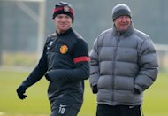 Manchester United manager Alex Ferguson (R) and player Wayne Rooney attend a training session in Manchester on March 4, 2013, ahead of their Champions League match against Real Madid. Real's victories over Barcelona have given them momentum ahead of their clash at United on Tuesday