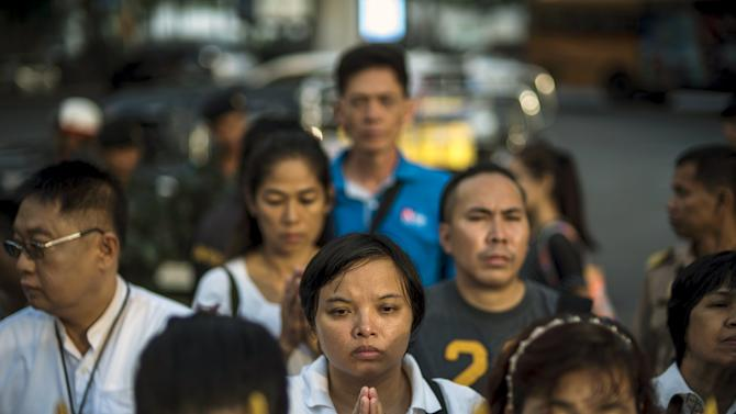 People pray during a religious ceremony at the Erawan shrine in central Bangkok