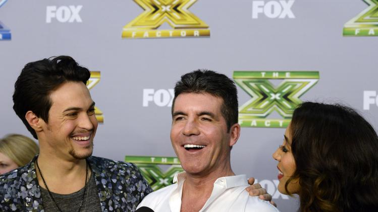 "Alex Kinsey and Sierra Deaton look at their mentor and judge Simon Cowell as he speaks during an interview backstage after the folk duo won ""The X Factor """