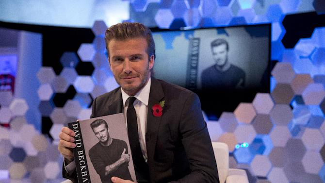 """Former England national soccer team captain David Beckham poses for photographs with a copy of his new photography book entitled """"David Beckham"""" after being interviewed by The Associated Press at a studio in Hampstead, north London, Wednesday, Oct. 30, 2013. (AP Photo/Matt Dunham)"""