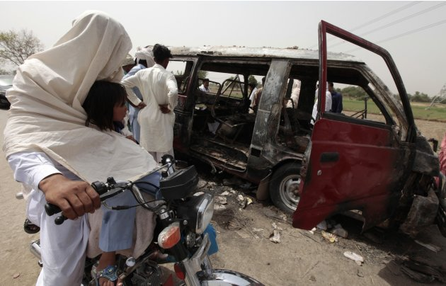 A man and his daughter ride a motorcycle past a burnt-out school bus after a gas cylinder on it exploded killing seventeen children on the outskirts of Gujrat