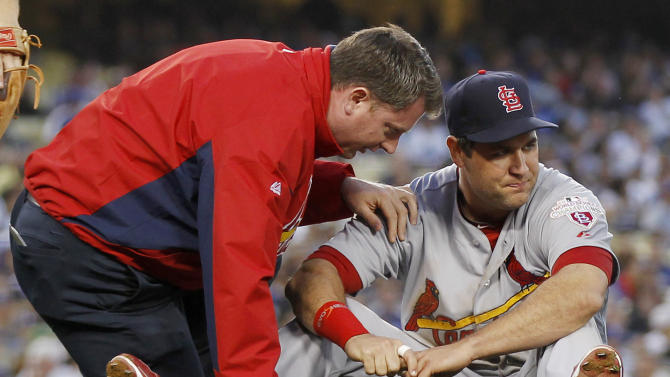 A trainer checks the right knee of St. Louis Cardinals first baseman Lance Berkman, right, who sustained an injury while forcing out Los Angeles Dodgers' Justin Sellers at first base to end the second inning of a baseball game on Saturday, May 19, 2012, in Los Angeles. (AP Photo/Danny Moloshok)