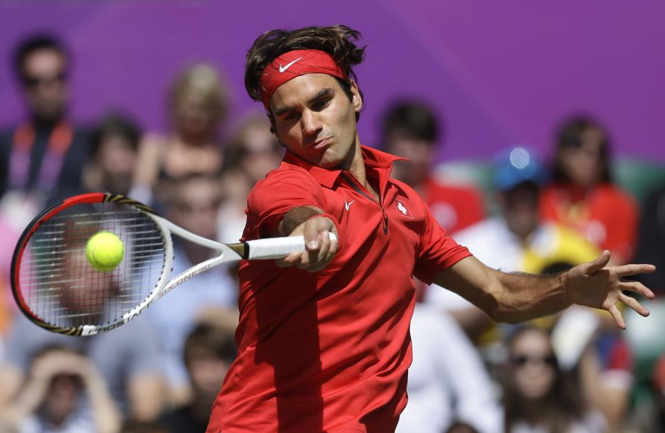 Switzerland's Roger Federer returns a shot to Britain's Andy Murray during the men's singles gold medal match at the All England Lawn Tennis Club at Wimbledon, in London, at the 2012 Summer Olympics, Sunday, Aug. 5, 2012. (AP Photo/Victor R. Caivano)