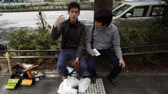 Canadian Jastin Leung answers questions from a journalist as they sit next to Leung's foldable chairs and plastic bags containing 10 of Apple's new iPhone 6 and 6 plus, near the Apple Store at Tokyo's Omotesando shopping district