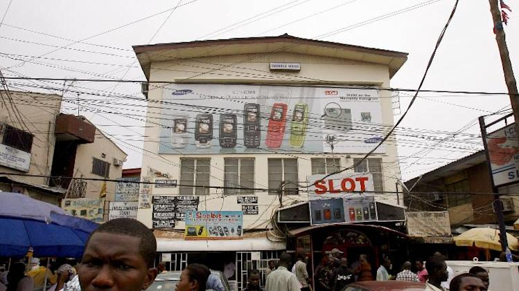 People walk by a shop at a market in Lagos on April 23, 2007