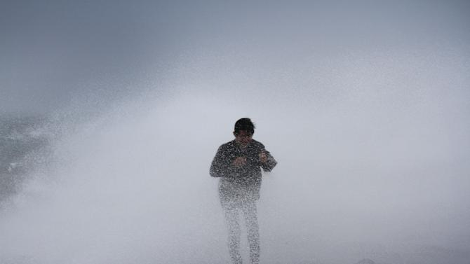 A resident stands near waves in Legazpi City, southeast of Manila, on July 15, 2014 as authorities warned of approaching Typhoon Rammasun