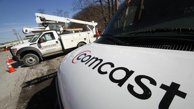 FILE - In this Feb. 15, 2011 file photo, Comcast logos are displayed on installation trucks in Pittsburgh. Cable giant Comcast Corp., the nation's largest provider of TV and high-speed Internet services, more than doubled its net income in the third quarter, helped by fewer cancelations of video service than expected and by breaking even on the expensive-to-produce London Olympics on NBC. (AP Photo/Gene J. Puskar, File)
