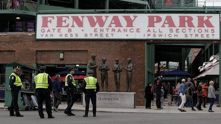 Police officers stand near statues of fromer Boston Red Sox greats, from left, Ted Williams, Bobby Doerr, Johnny Pesky and Dom DiMaggio during a baseball game between the Kansas City Royals and the Boston Red Sox, the first game held in the city following the Boston Marathon explosions, Saturday, April 20, 2013, in Boston.  Police captured Dzhokhar Tsarnaev, 19, the surviving Boston Marathon bombing suspect, late Friday, after a wild car chase and gun battle earlier in the day left his older brother dead.  (AP Photo/Julio Cortez)
