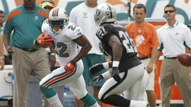 Miami Dolphins running back Reggie Bush (L) tries to elude Oakland Raiders cornerback Lito Sheppard after picking up a first down during their NFL football game in Miami, Florida, December 4, 2011