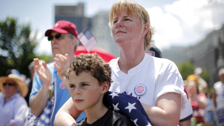 Deb Mirenda of Coatesville, Pa. and her son Vincent, 9,  listen to a speaker, during a protest against the Obama administration mandate that employers provide workers birth control coverage, at Independence Mall, Friday, June 8, 2012, in Philadelphia. The event was organized by Stand Up For Religious Freedom. (AP Photo/Matt Rourke)