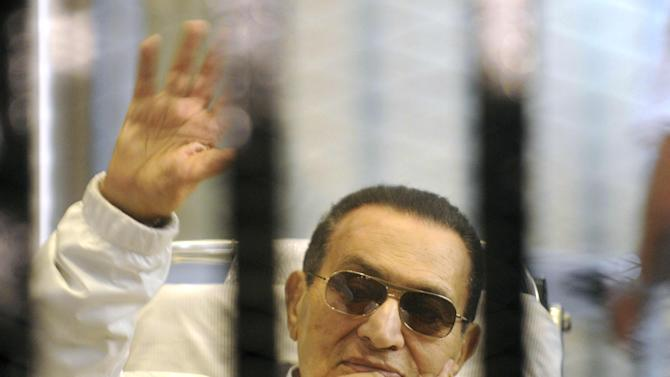 Former Egyptian President Hosni Mubarak waves to his supporters from behind bars as he attends a hearing in his retrial on appeal in Cairo, Egypt, Saturday, April 13, 2013. Egypt's highest court in January ordered a retrial for Mubarak, for failing to stop the killing of 900 protestors in the 2011 unrest that ousted him, after accepting an appeal against his life sentence, citing procedural failings. A high-level inquiry into the deaths of the nearly 900 protesters killed in the uprising, parts of which were released exclusively to The Associated Press last month, could weigh heavily in the retrial. (AP Photo)