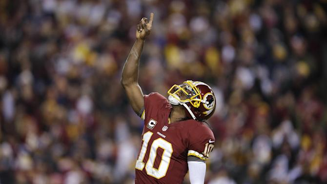 Washington Redskins quarterback Robert Griffin III celebrates a touchdown during the first half of an NFL football game against the Dallas Cowboys on Sunday, Dec. 30, 2012, in Landover, Md. (AP Photo/Evan Vucci)