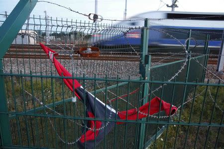 A TGV high speed train passes behind razor-wire fencing close to the Channel Tunnel site on which a sweat shirt is stretched over the barbs to protect asylum seekers who climb over the fence in Calais