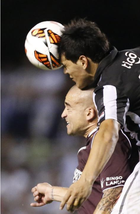 Gustavo Gomez of Paraguay's Libertad, top, heads the ball alongside Santiago Silva of Argentina's Lanus at a Copa Sudamericana soccer game in Asuncion, Paraguay, Thursday, Nov. 21, 2013