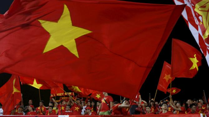 Vietnamese fans wave their country's national flag during the 2018 World Cup Group F qualifying soccer match against Iraq at My Dinh Stadium in Hanoi
