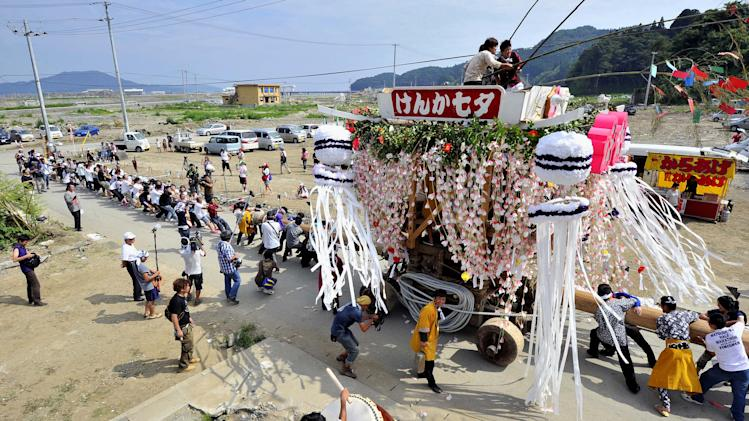Residents and tourists pull a decorated float in the tsunami-hit Rikuzentakata city, northeastern Japan, during the Fighting Star Festival  Sunday, Aug. 7, 2011. The only one float paraded through the city this year, because the March 11 tsunami swept away other three floats. The annual festival, which local elders say dates back to 900 years, is famous for bumping of the floats during processions.  (AP Photo/Kyodo News) JAPAN OUT, MANDATORY CREDIT, NO LICENSING IN CHINA, FRANCE, HONG KONG, JAPAN AND SOUTH KOREA