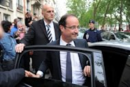 Newly elected president Francois Hollande leaves his campaign headquarters in Paris, one day after the announcement of the first official results of the French presidential second round