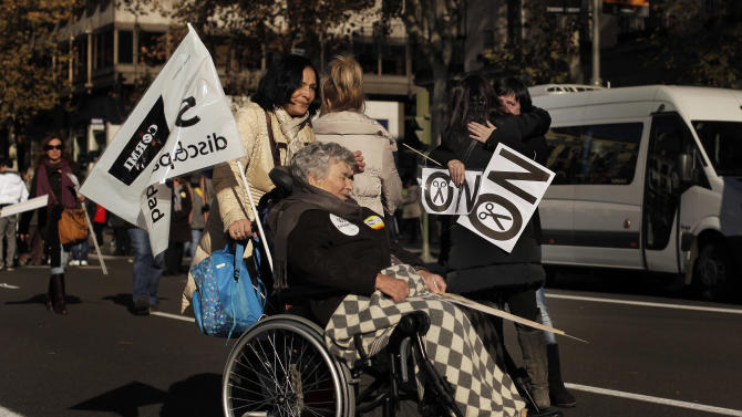 "People gesture as they carry banners reading, ""SOS, disability"" and ""No financial cuts"" during a protest against government austerity measures affecting disabled people by reducing services, closing disability centers and forcing care workers from their jobs in Madrid, Spain, Sunday, Dec. 2, 2012. More than 10,000 people, many in wheelchairs or being led by guide dogs, marched in a demonstration with the slogan ""SOS Disability: Save our Rights, Inclusion and Welfare."" Health care spending falls under the responsibility of regional governments, many of which are indebted. Some local administrations have failed to pay medical centers, forcing cuts in services and a slow-down in the distribution of medicine. (AP Photo/Andres Kudacki)"