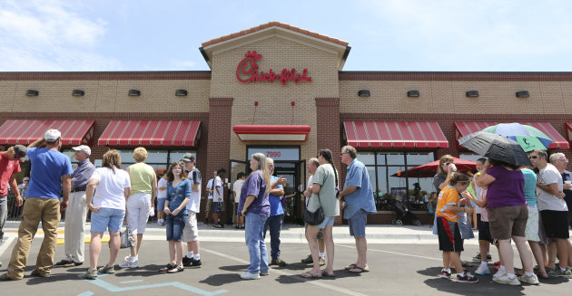 "<p>               Customers stand in line for a Chick-fil-a meal at the chain's restaurant in Wichita, Kan., on Wednesday. Aug. 1, 2012. The crowd was buying meals to show their support for the company that's currently embroiled in a controversy over same-sex marriage.   Former Arkansas Gov. Mike Huckabee, a Baptist minister, declared Wednesday national ""Chick-fil-A Appreciation Day."" Opponents of the company's stance are planning ""Kiss Mor Chiks"" for Friday, when they are encouraging people of the same sex to show up at Chick-fil-A restaurants around the country and kiss each other. (AP Photo/The Wichita Eagle, Travis Heying)"