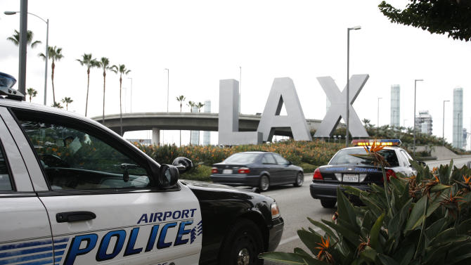 FILE - In a Dec. 26, 2009 file photo, airport police monitor the entrance of Los Angeles International Airport in Los Angeles. Yongda Huang Harris, 28, flying from Japan to Boston, was arrested Friday, Oct. 5, 2012, during a stopover at Los Angeles International Airport, wearing a bulletproof vest and flame-resistant pants, and travelling with a suitcase full of weapons, leg irons, a smoke grenade, a gas mask and a biohazard suitd, U.S. Immigration and Customs Enforcement officials said Tuesday, Oct. 10, 2012. (AP Photo/Jason Redmond, File)
