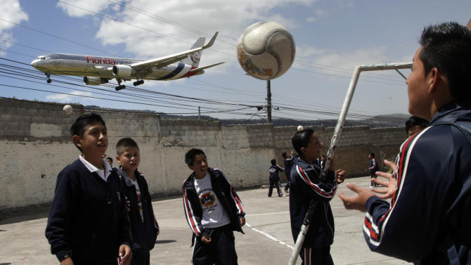In this Jan. 8, 2013 photo, students play soccer at their school, Eloy Alfaro, as a plane approaches the Mariscal Sucre airport for landing in Quito, Ecuador. Mariscal Sucre airport sat amid cornfields when it was christened in 1960.  On Feb. 19, the airport will close and a new airport will be built in an agricultural setting 12 miles (20 kilometers) northeast of the city. While the old airport can be reached from downtown in 20 minutes or so it will take at least an hour to get to the new airport, and no train-to-the-plane is yet planned. (AP Photo/Dolores Ochoa)