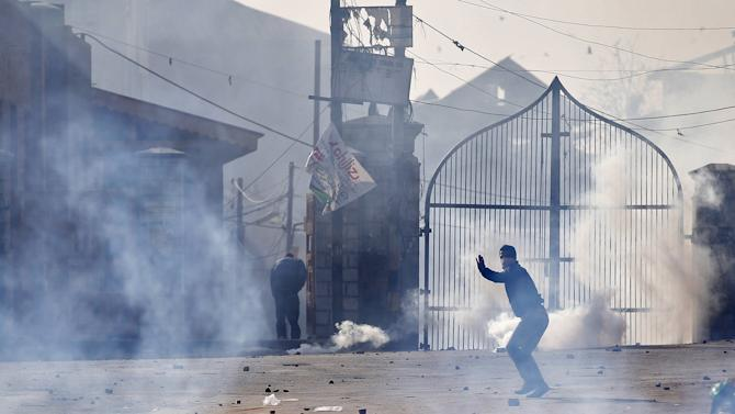 A protester throws a stone towards Indian police as he is surrounded by teargas during a demonstration in Srinagar