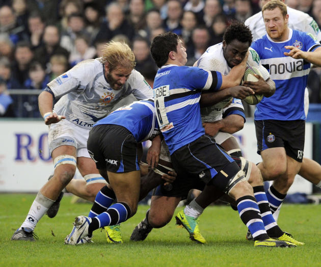 Bath's Francois Louw, centre, and Olly Woodburn, 2nd left, tackle Montpellier's Remy Martin during their Heineken Cup pool 3 rugby match at the Recreation ground, Bath, England, Sunday, Nov. 20, 2011.
