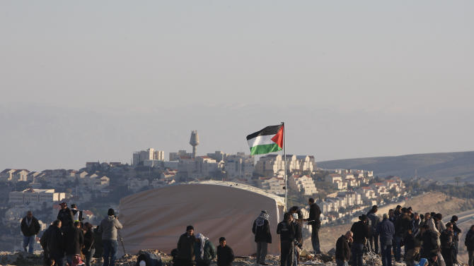 Palestinians, together with Israeli and foreign activists, stand near newly-erected tents in an area known as E1 and in the background the Israeli settlement of Ma'aleh Adumim is seen, near Jerusalem, Friday, Jan 11, 2013.Palestinian activists pitched tents in the West Bank on Friday to protest Israeli plans to build a large Jewish settlement on a key route through the territory. The E-1 settlement would block east Jerusalem from its West Bank hinterland — both territories captured by Israel during the 1967 Mideast war. (AP Photo/Majdi Mohammed)