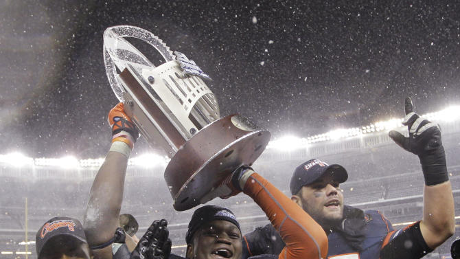 From left, Syracuse safety Shamarko Thomas (21), linebacker Siriki Diabate and left tackle Justin Pugh celebrate with the trophy after Syracuse defeated West Virginia 38-14 in the Pinstripe Bowl NCAA college football game at Yankee Stadium in New York, Saturday, Dec. 29, 2012. (AP Photo/Kathy Willens)