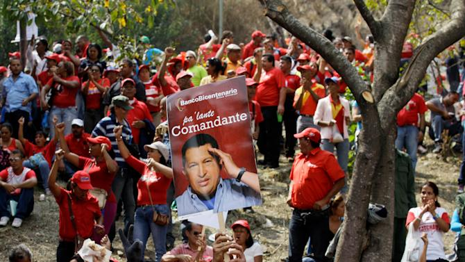 FILE - In this Jan. 23, 2013 file photo, a supporter of Venezuela's President Hugo Chavez holds up a poster of Chavez at an event commemorating the 1958 fall of the country's dictatorship in Caracas, Venezuela. The long and at times surreal saga surrounding the cancer treatment of President Hugo Chavez has many Venezuelan writers and intellectuals likening the nation's drama to a telenovela. Venezuela has long produced soap operas, and some say no one could have imagined a more bizarre plot than the one unfolding in the more than seven weeks since Chavez traveled to Cuba for his operation and disappeared from public view.  (AP Photo/Fernando Llano, File)