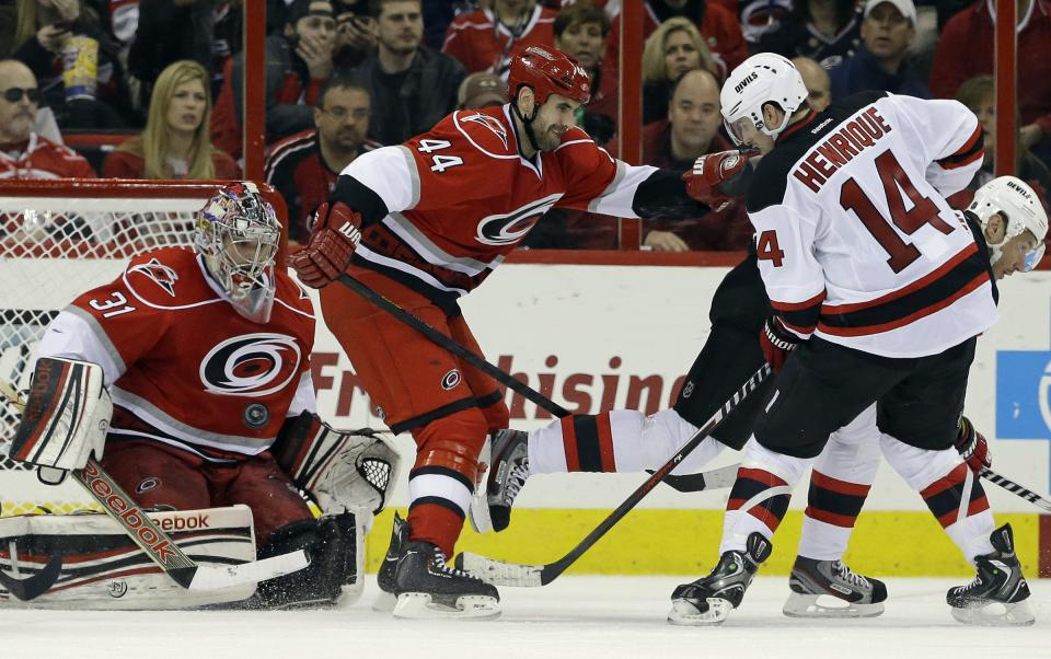 Carolina Hurricanes goalie Dan Ellis (31) and teammate Jay Harrison (44) defend against New Jersey Devils' Adam Henrique (14) during the second period of an NHL hockey game in Raleigh, N.C., Thursday, March 21, 2013. Henrique scored on the play. (AP Photo/Gerry Broome)