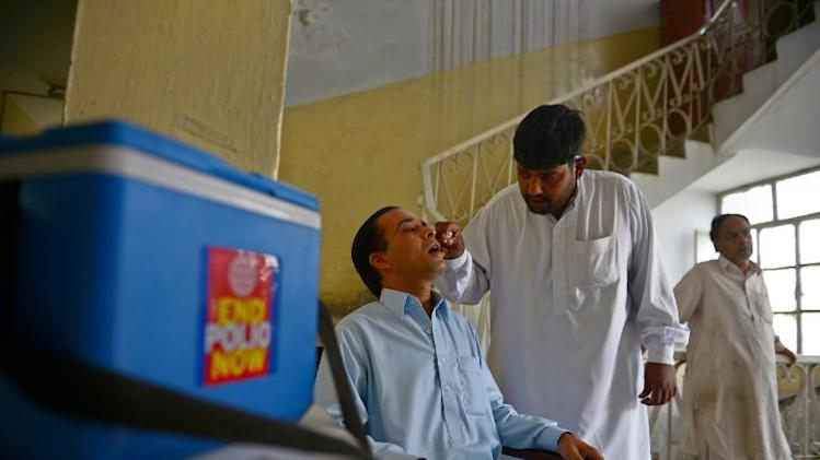 A Pakistani health worker (C) administers polio vaccination drops to a traveller planning a trip abroad, at the DHQ hospital in Rawalpindi on May 19, 2014
