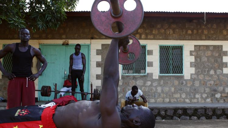 A kick-boxer lifts weights during a practice session at a sports centre in Juba