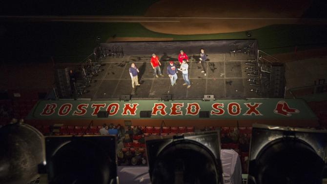 "Actors perform on a stage in front of the Red Sox dugout during the Commonwealth Shakespeare Company's production ""Shakespeare at Fenway"" at Fenway Park in Boston"