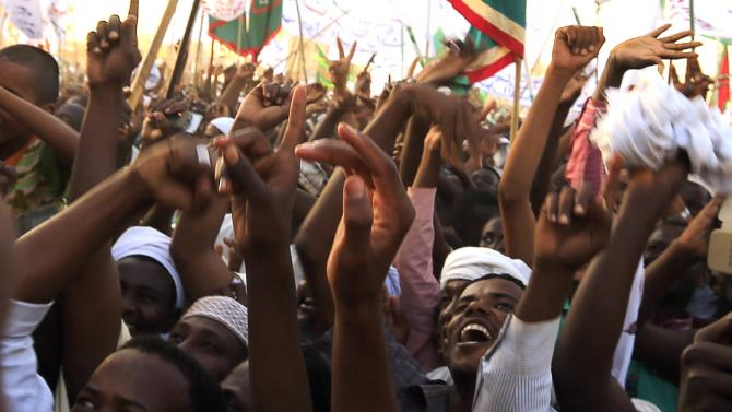 Supporters wave as Sudanese President Omar Hassan al-Bashir attends a rally with Sufi supporters Hajj Yusuf at Khartoum district