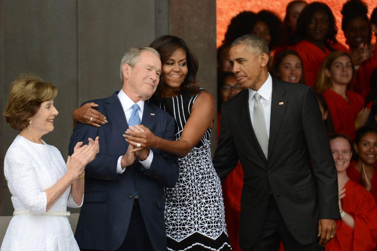 Why President Obama helping George W. Bush take a photo strikes such a chord