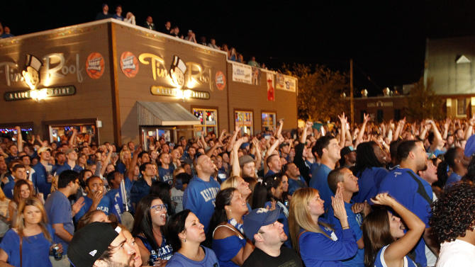 Kentucky fans cheer as they watch television coverage of the NCAA men's college basketball tournament Final Four title game in New Orleans between Kentucky and Kansas, at Tin Roof on Monday night, April 2, 2012, in Lexington, Ky. (AP Photo/The Courier-Journal, James Crisp) MAGS OUT  NO SALES  ARCHIVE OUT  MANDATORY CREDIT