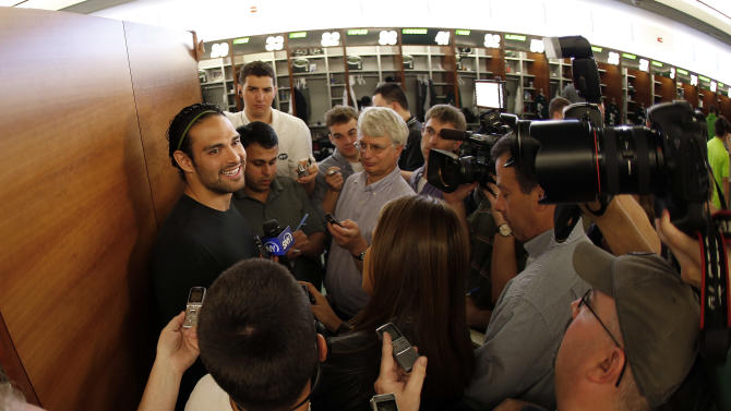 In this image taken with a fisheye lens,New York Jets quarterback Mark Sanchez, left, talks to reporters during a locker room availability at the team's NFL practice practice facility in Florham Park, N.J., Thursday, May 2, 2013. The Jets may have cut Tim Tebow but their situation at quarterback is far from settled. New general manager John Idzik says Sanchez, David Garrard, Greg McElroy, Matt Simms and second-round draft pick Geno Smith are all candidates to be the starter. (AP Photo/Rich Schultz)