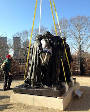 """Auguste Rodin's """"The Burghers of Calais"""" is set down with a giant crane Friday, March 22, 2013 outside the Rodin Museum in Philadelphia, which reopened last summer after a three-year renovation inside and out. The sculpture is outdoors in the museum's garden, where it was first installed in 1929. It came indoors in the 1960s because the elements were taking a toll on the 6,000-pound bronze sculpture. Conservators say technological advances allowed them to remove corrosion from the """"The Burghers"""" with lasers and chemical compounds. A new coating system will protect the sculpture from future weathering.  (AP Photo/JoAnn Loviglio)"""