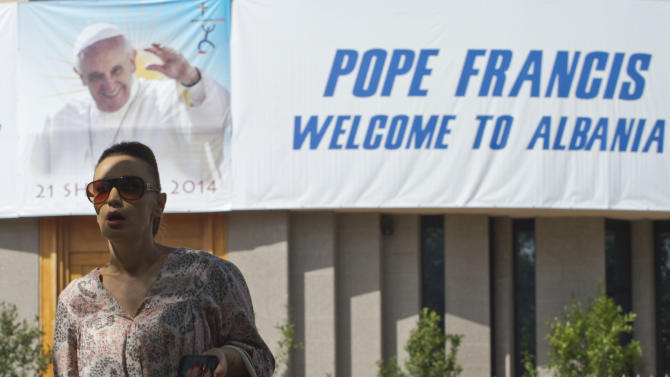 An Albanian woman walks past a poster hanging from the entrance of a Catholic church welcoming Pope Francis, in Tirana, Albania, Friday, Sept. 19, 2014. Pope Francis will travel to Albania Sunday for a one-day trip. Francis has said he wanted to visit Albania to highlight the rebirth of Christianity that was brutally wiped out during communist rule, and to showcase how Catholics, Orthodox and Muslims are working together now to govern the country. (AP Photo/Visar Kryeziu)