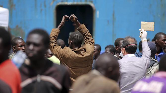 Migrants stand on the dock after disembarking from a merchant ship at the Sicilian harbour of Catania