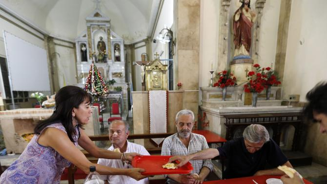 A volunteer distributes a Christmas meal to impoverished people at the parish church San Pedro de La Boca in Buenos Aires