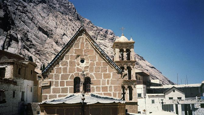 FILE - In this Jan. 1, 1985 file photo, St. Catherine the highest mountain in the biblical land of Sinai, overlooking a 1,450-years old monastery in Egypt. Egyptian security officials said Monday that they will not give in to the demands of a Bedouin man who took hostage two Americans and their local translator, now entering their fourth day in captivity. Boston-area residents Pentecostal Rev. Michel Louis, 61, and 39-year-old Lissa Alphonse were taken off a bus Friday with their Egyptian tour guide on a road in the Sinai Peninsula. The two Americans were on a Holy Land tour heading from Cairo to the sixth-century St. Catherine's Monastery, located at the foot of Mount Sinai where the Old Testament says Moses received the stone tablets with the Ten Commandments. (AP Photo/Paola Crociani, File)