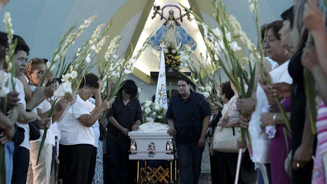Relatives and friends mourn next to the coffin of Martha Armadillo, one of the pilgrims who died in an accident, after her funeral mass at a church in Monterrey, Mexico